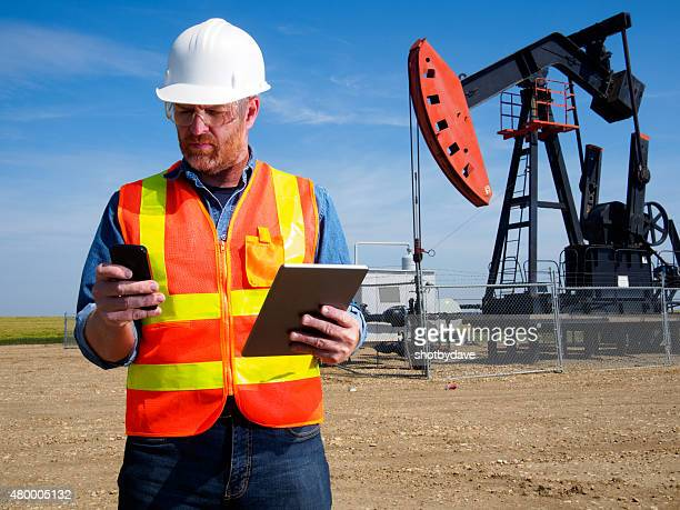 Oil Engineer with Tablet Computer and Pumpjack