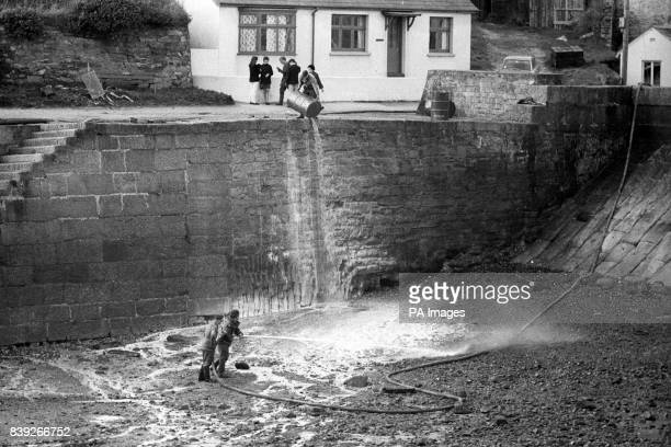 Oil from the tanker Torrey Canyon glistens on rocks as troops spray detergent at the small beach and bathing area of Dollar Cove in the Cornish...
