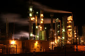 Refinery at night with lights and smoke streams