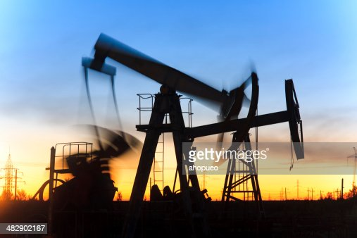 Oil jack silhouette in motion during beautiful sunset