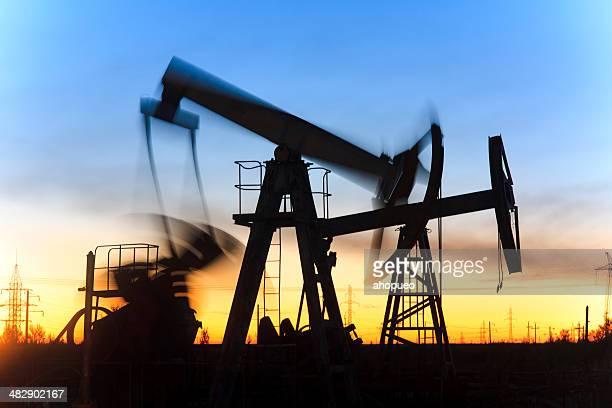 Oil jack-silhouette in Bewegung während Sonnenuntergang