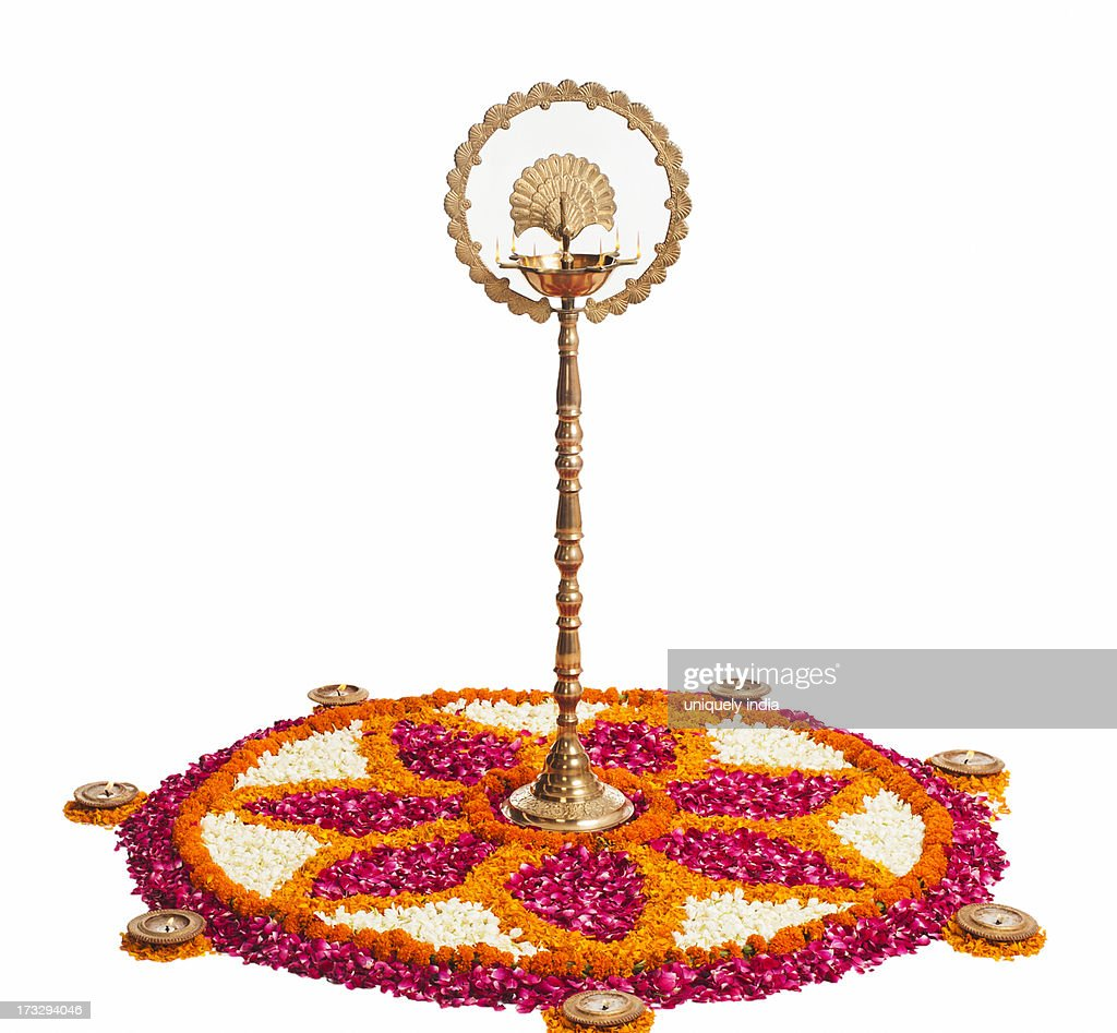 Oil lamps and rangoli of flowers at Onam