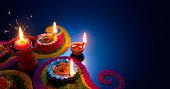 Oil lamps lit on colorful rangoli during diwali celebration