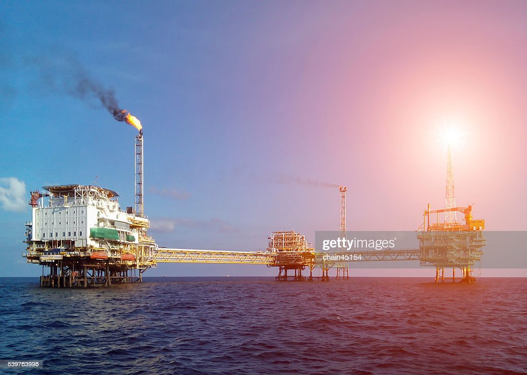 Oil Platform, Offshore oil and rig platform in sunset or sunrise time. Construction of production process in the sea. Power energy of the world, Oil production and the pipe in the sea, fuel energy.