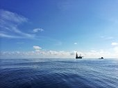 Oil platform with supply vessel nearby during daytime