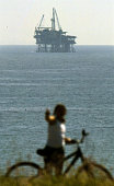Oil platforms of the Southern California Coast in the Santa Barbara Channel Bicyclist on a bluff in Carpinteria looking out to an oil platform in the...
