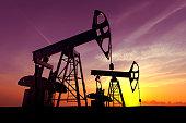 Oil pump against sunset sky.