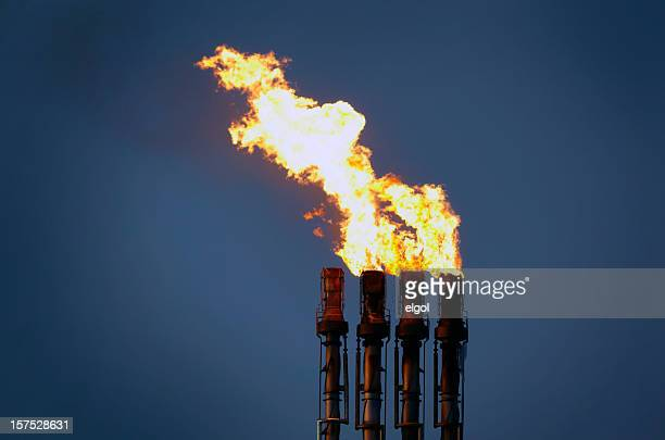 Oil refinery flare stack at night with flames and pollution