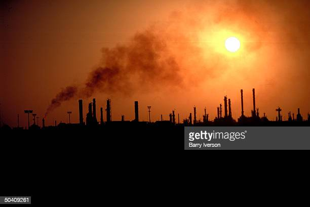 Oil refinery outside city in panoramic silhouette against setting/rising sun