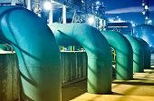 Close-up oil refinery pipeline equipment at night.
