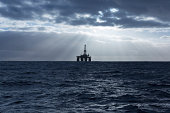 oil rig at sea with sun shining through clouds