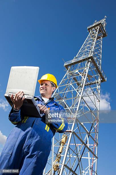 Oil Rig Worker at a Well with Computer Checking Email