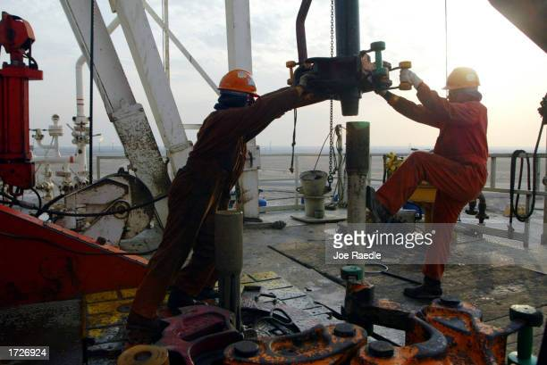 Oil rig workers work on the ChevronTexaco drilling platform January 15 2003 near the Saudi Arabian border Kuwait Kuwait produces 10% of the worlds...