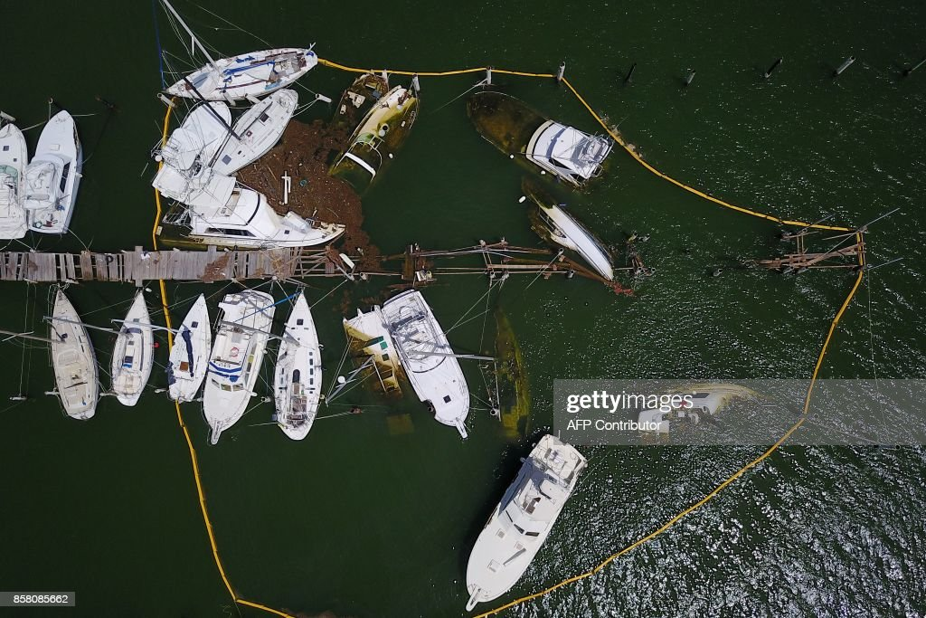 TOPSHOT - Oil spill containment barriers surround sunk and damaged boats affected by the passing of Hurricane Maria in Fajardo, Puerto Rico on October 4, 2017. US President Donald Trump on asked Congress for a bumper $29 billion package of emergency relief after Hurricane Maria slammed into Puerto Rico. Hurricane Maria not only destroyed Puerto Rico's infrastructure, it also wreaked havoc on the environment, disrupting the island's entire ecosystem. But life has been thrown into turmoil for birds, insects and other organisms that depend on leaves and flowers for food and shelter. They struggle to find food and places to hide. / AFP PHOTO / Ricardo ARDUENGO