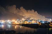 Oil storage tanks and smoke stacks on Puget Sound waterfront at night, Tacoma, Washington State, USA