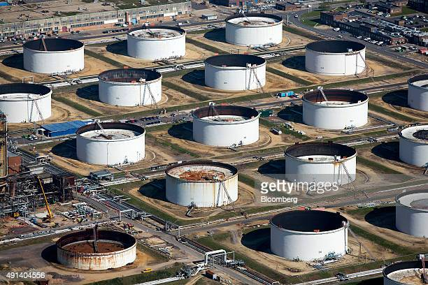 Oil storage tanks sit at the Esso oil refinery operated by Exxon Mobil Corp in Fawley UK on Friday Oct 2 2015 A 50 percent drop in crude prices in...