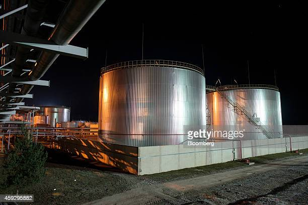 Oil storage tanks sit illuminated against the night sky at Eesti Energia AS's Enefit 280 oil shale processing plant and energy production facility in...