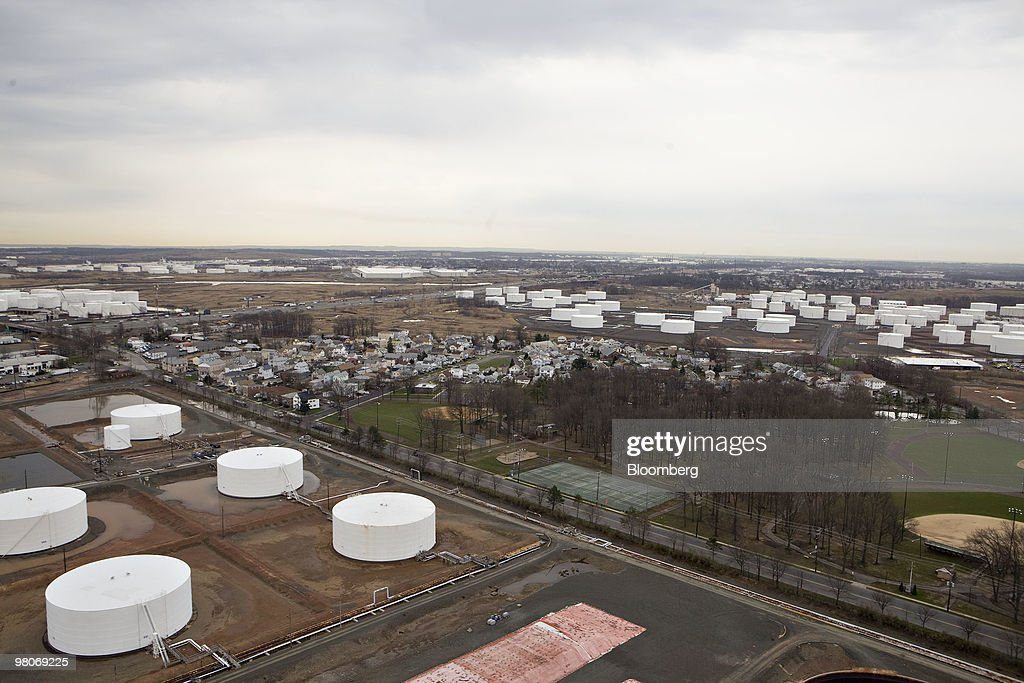 Oil storage tanks surround a residential area as viewed from an A-star 350 B-2 helicopter made by Eurocopter SA, one of six in the fleet of Liberty Helicopters Inc., as it flies over Linden, New Jersey, U.S., on Thursday, March 25, 2010. Liberty Helicopters Inc. is offering to fly weary commuters from New Jersey to Manhattan for about $200 a day, saving them 14 hours in traffic a week and signaling that Wall Street may have seen the worst of the recession. Photographer: Daniel Acker/Bloomberg via Getty Images