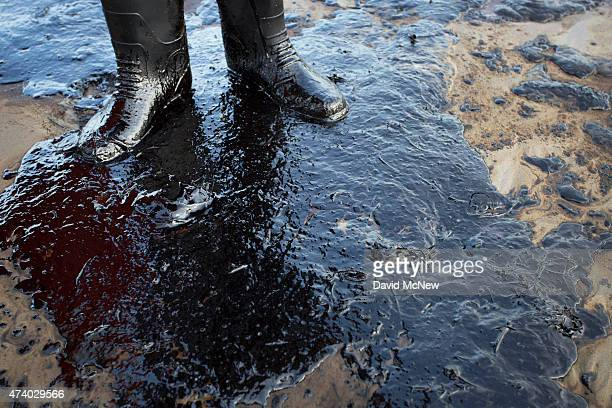 Oil surrounds the feet of local resident Morgan Miller as he patrols the beach for oiled wildlife on May 19 2015 north of Goleta California About...