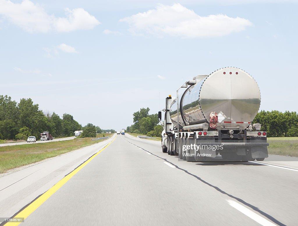 Oil tanker semi truck driving down highway