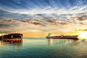Two tanker ships on sea in the rays of the setting sun.