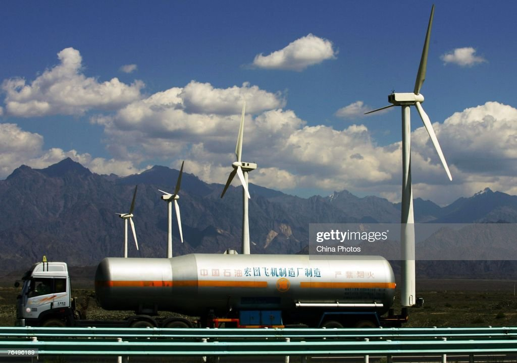 A oil truck runs past wind turbines at the Dafancheng Wind Power Plant the largest of its kind in Aisa on September 2 2007 in Dafancheng of Xinjiang...
