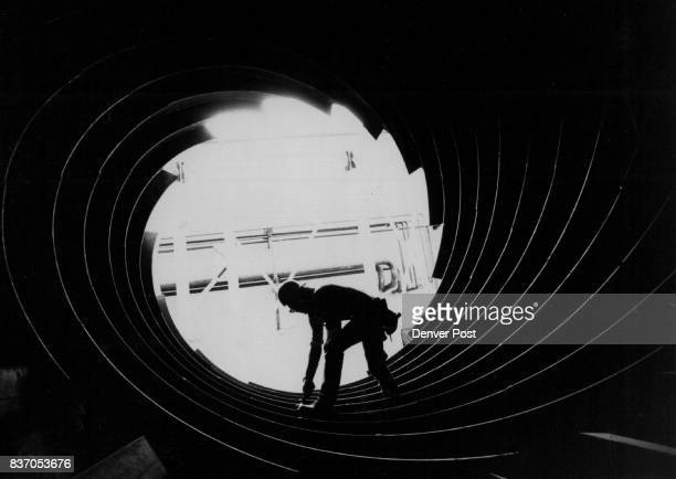 Oil worker has an inside job The helical innards of a huge heater silhouettes worker at Green River Wyo where Tenneco Oil Co is conducting a trona...