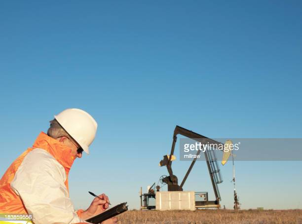 Oil Worker in Safety Gear at Well Pumpjack