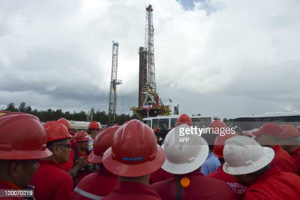 Oil workers gather by an oil well operated by Venezuela's stateowned oil company PDVSA in Morichal Venezuela on July 28 2011 Venezuela will fulfill...