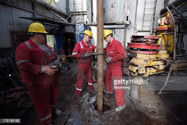 Oil workers prepare drill pipes for operation on the floor of a drilling rig operated by Salym Petroleum in Salym KhantyMansi autonomous region...