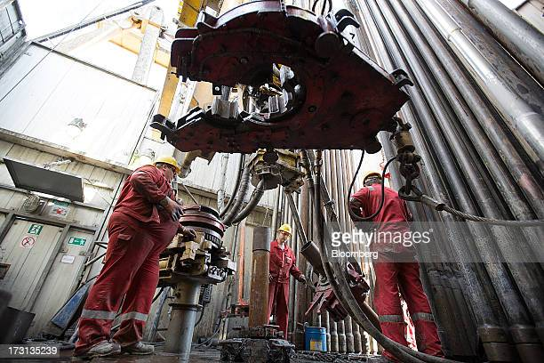 Oil workers use machinery to move drill sections on the drilling floor of a derrick operated by Salym Petroleum in Salym KhantyMansi autonomous...