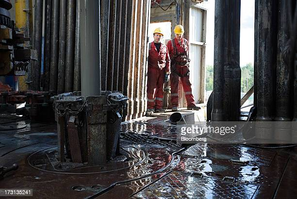 Oil workers watch the operation of the drill pipe on the floor of a derrick operated by Salym Petroleum in Salym KhantyMansi autonomous region Russia...