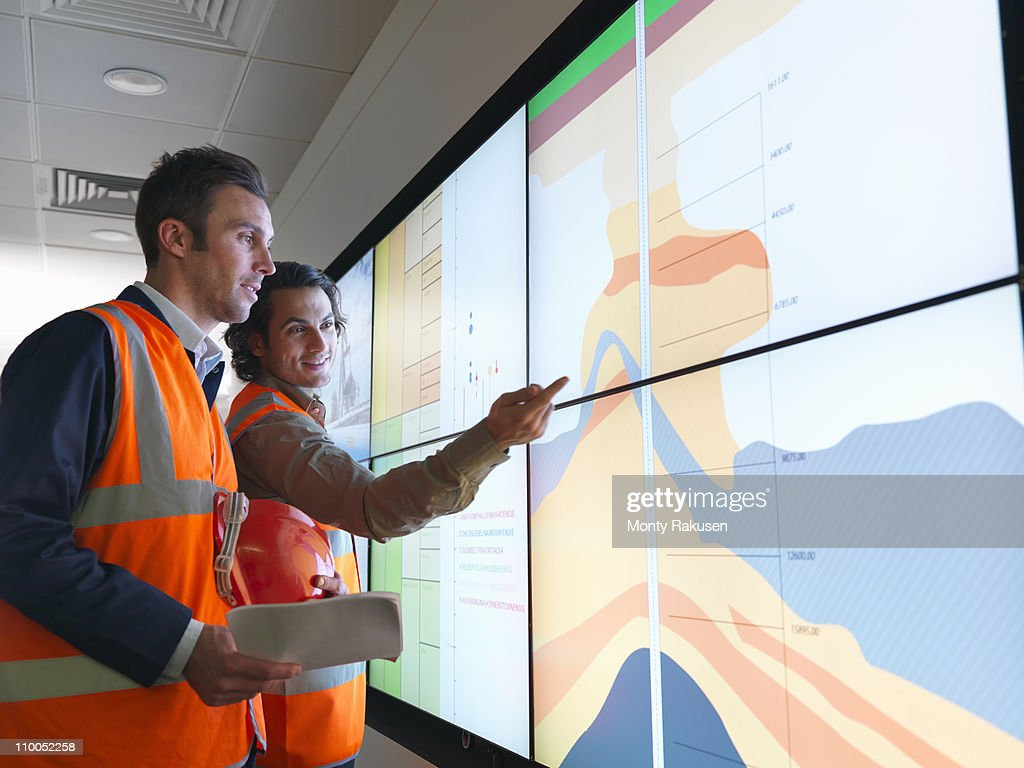 Oil workers with geology screen : Stock Photo