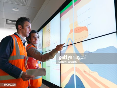 Oil workers with geology screen