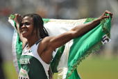 Okabare Blessing of Nigeria celebrates with the Nigerian flag after crossing the finish line in first place in the Women's 100 metres final during...