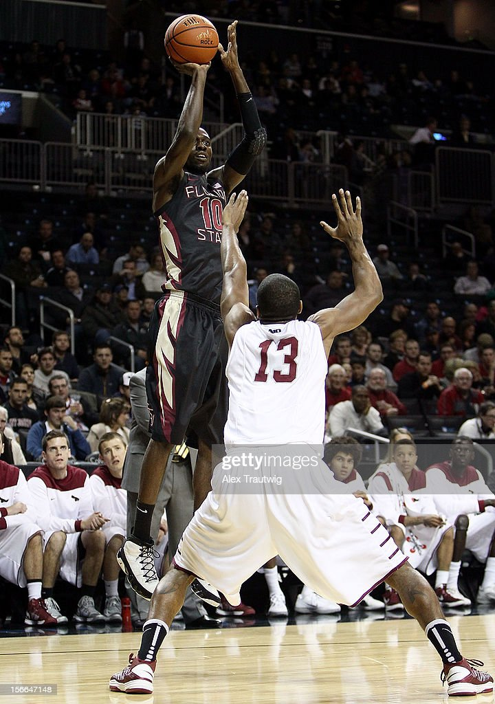Okaro White #10 of the Florida State Seminoles takes a shot over Ronald Roberts Jr. #13 of the Saint Joseph's Hawks during the championship game of the Coaches Vs. Cancer Classic at the Barclays Center on November 17, 2012 in the Brooklyn borough of New York City.