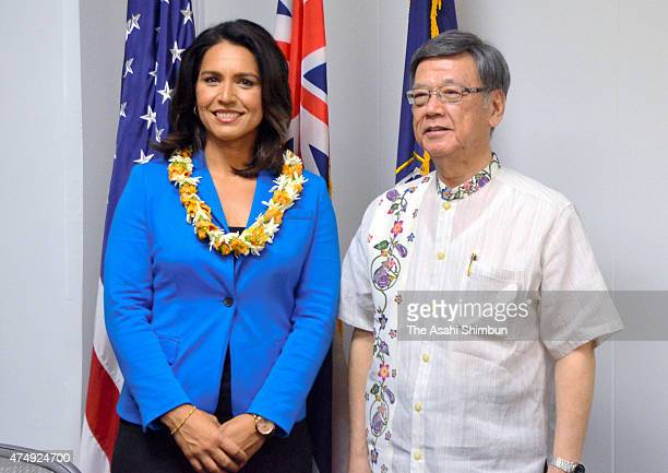 Okinawa Prefecture governor Takeshi Onaga and US congresswoman Tulsi Gabbard pose for photographs during their meeting on May 27 2015 in Honolulu...
