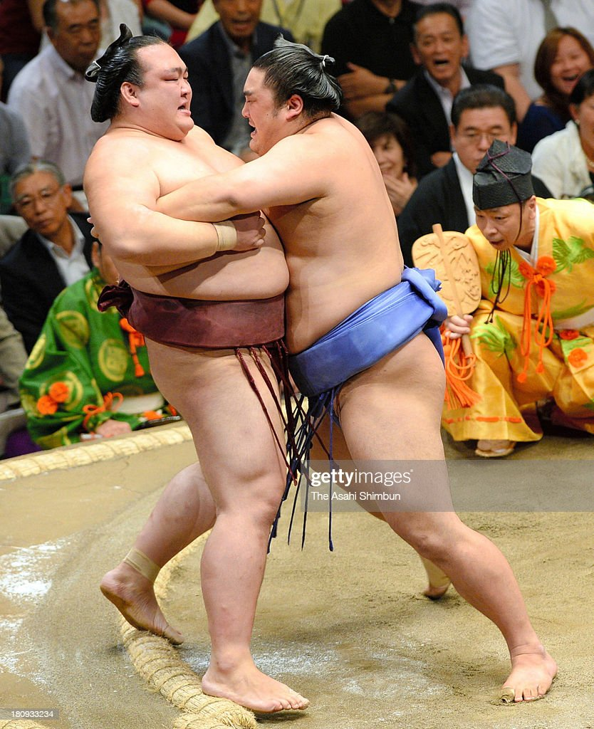 Okinoumi (R) pushes ozeki Kisenosato out of the ring during day three of the Grand Sumo Autumn Tournament at Ryogoku Kokugikan on September 17, 2013 in Tokyo, Japan.
