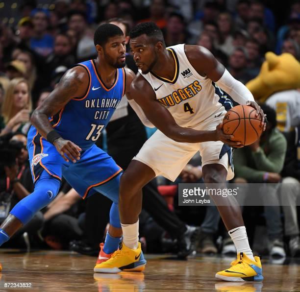 Oklahoma City Thunder forward Paul George guards Denver Nuggets forward Paul Millsap during the fourth quarter on November 9 2017 in Denver Colorado...