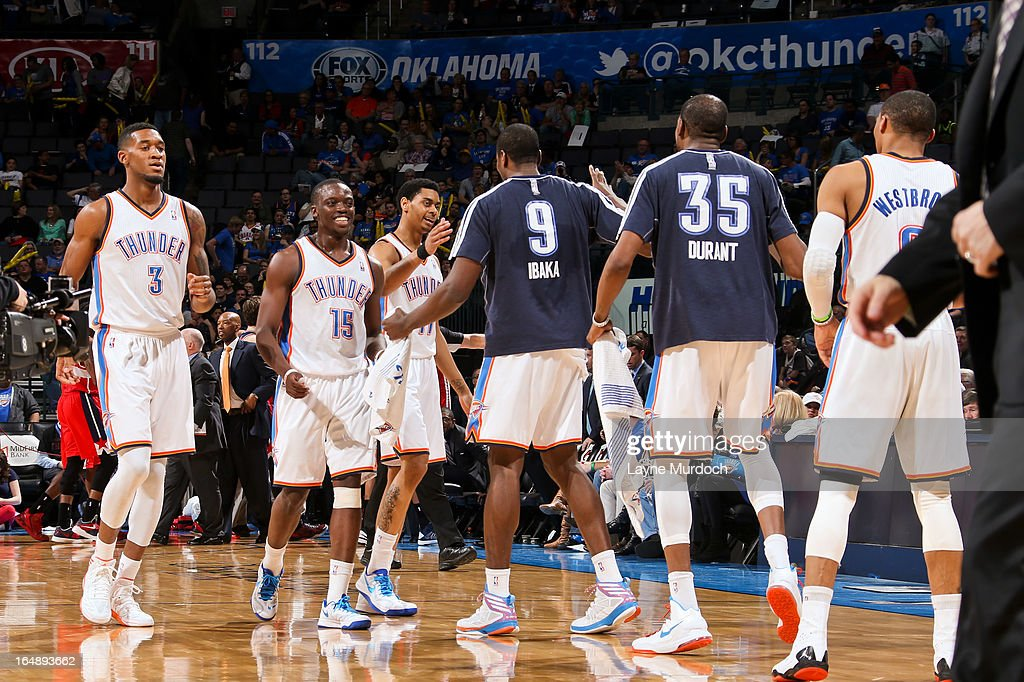 Oklahoma City Thunder players, from left, Perry Jones #3, Reggie Jackson #15, Jeremy Lamb #11, Serge Ibaka #9, Kevin Durant #35 and Russell Westbrook #0 celebrate during a timeout in a game against the Washington Wizards on March 27, 2013 at the Chesapeake Energy Arena in Oklahoma City, Oklahoma.