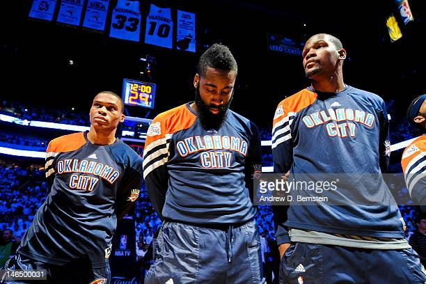 Oklahoma City Thunder players from left Russell Westbrook James Harden and Kevin Durant listen during the National Anthem before facing the Miami...