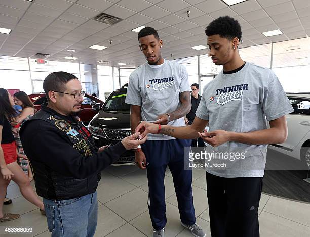 Oklahoma City Thunder players Jeremy Lamb and PJ Jones greet and hand out coupons to unsuspecting customers as they participate in the Thunder Random...