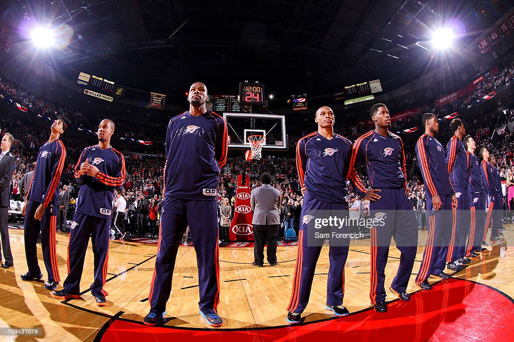 Oklahoma City Thunder players Kevin Durant #35, center left, and Russell Westbrook #0, center right, listen to the National Anthem before playing against the Portland Trail Blazers on January 13, 2013 at the Rose Garden Arena in Portland, Oregon.