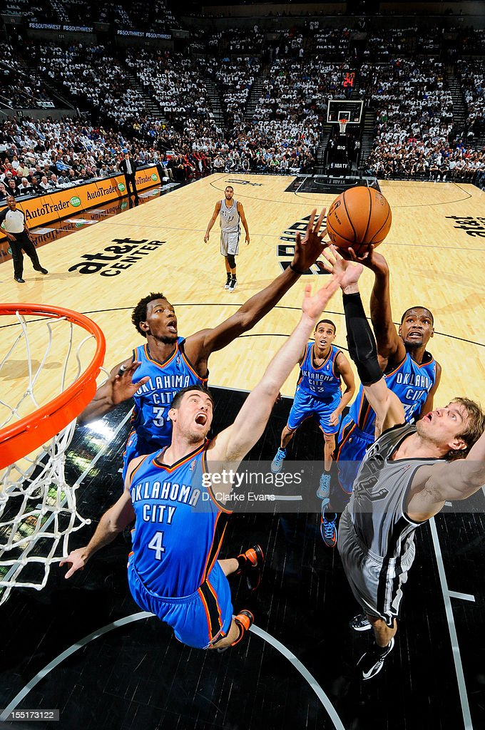 Oklahoma City Thunder players <a gi-track='captionPersonalityLinkClicked' href=/galleries/search?phrase=Nick+Collison&family=editorial&specificpeople=202843 ng-click='$event.stopPropagation()'>Nick Collison</a> #4, <a gi-track='captionPersonalityLinkClicked' href=/galleries/search?phrase=Hasheem+Thabeet&family=editorial&specificpeople=4003778 ng-click='$event.stopPropagation()'>Hasheem Thabeet</a> #34 and <a gi-track='captionPersonalityLinkClicked' href=/galleries/search?phrase=Kevin+Durant&family=editorial&specificpeople=3847329 ng-click='$event.stopPropagation()'>Kevin Durant</a> #35 go for a rebound against <a gi-track='captionPersonalityLinkClicked' href=/galleries/search?phrase=Tiago+Splitter&family=editorial&specificpeople=208218 ng-click='$event.stopPropagation()'>Tiago Splitter</a> #22 of the San Antonio Spurs on November 1, 2012 at the AT&T Center in San Antonio, Texas.