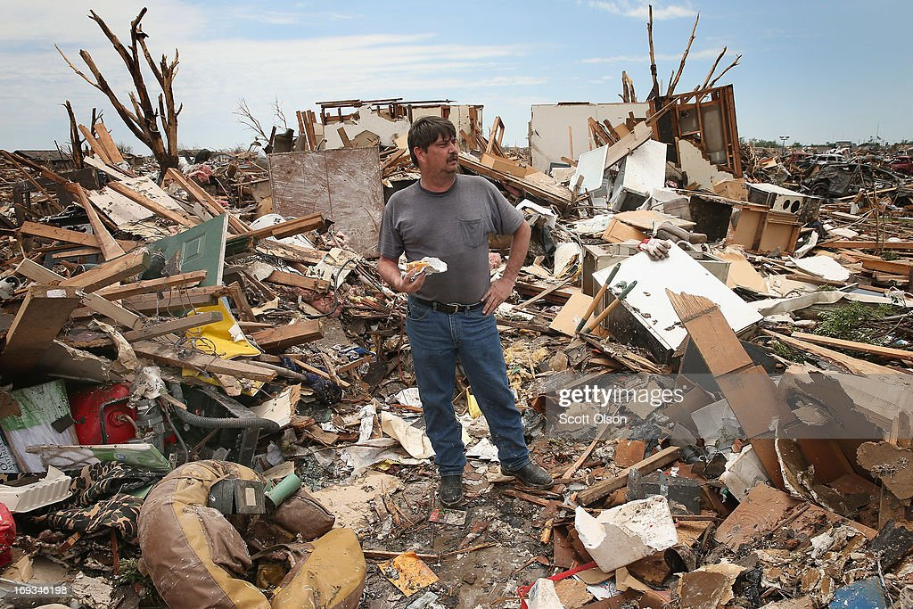 Oklahoma County sheriff's deputy Kirk Guarnera takes a lunch break in what is left of his home while he continues to salvage items after the home was destroyed by a tornado May 23, 2013 in Moore, Oklahoma. A two-mile wide EF5 tornado touched down in Moore May 20 killing at least 24 people and leaving behind extensive damage to homes and businesses. U.S. President Barack Obama promised federal aid to supplement state and local recovery efforts.