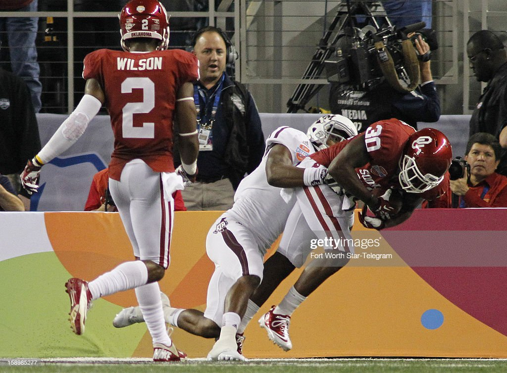 Oklahoma defensive back Javon Harris (30) is tackled in the end zone after intercepting Texas A&M quarterback Johnny Manziel in the second quarter in the AT&T Cotton Bowl game in Cowboys Stadium in Arlington, Texas, on Friday, January 4, 2013.