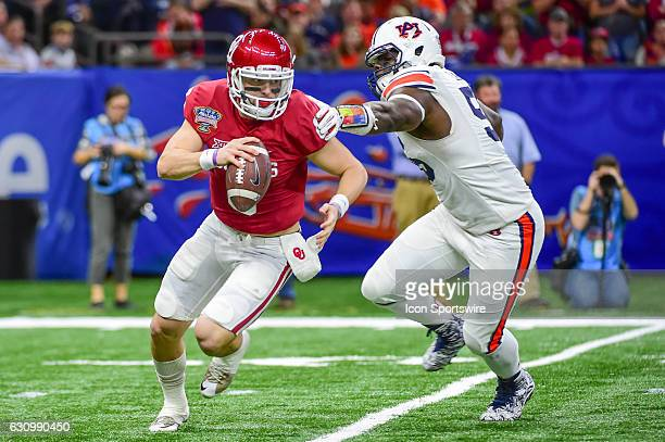 Oklahoma Sooners quarterback Baker Mayfield escapes the grasp of Auburn Tigers defensive lineman Carl Lawson during first half action during the...