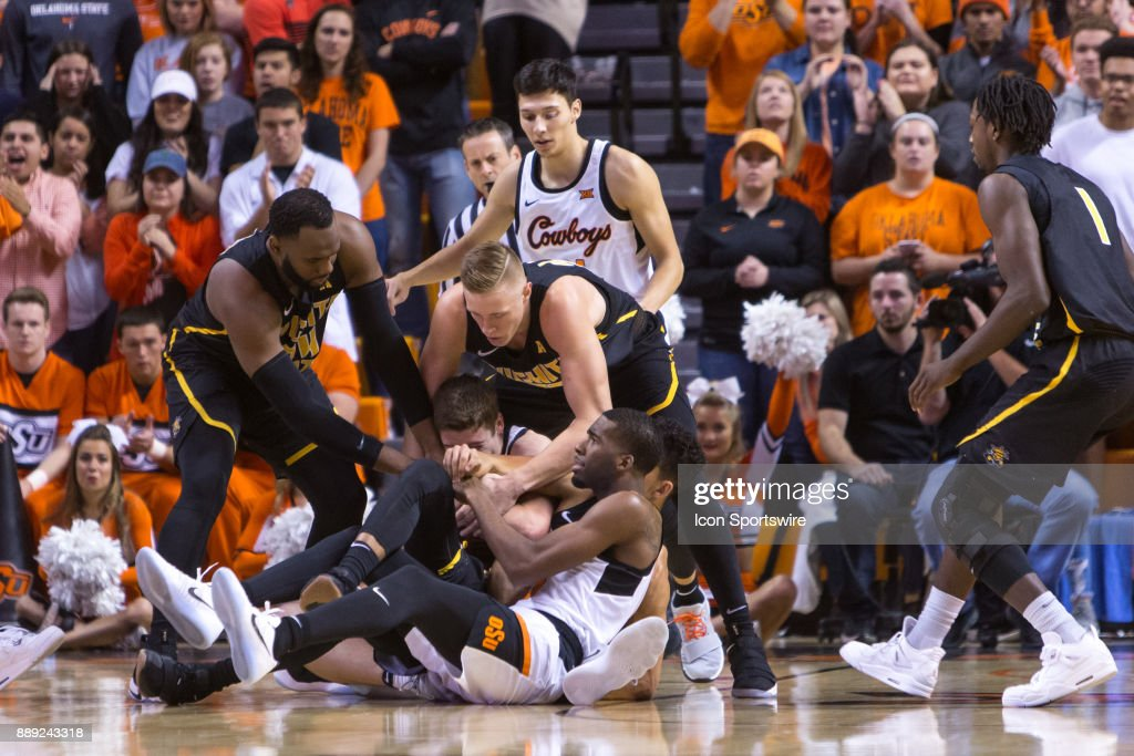 Oklahoma State Cowboys and Wichita State Shockers fight over a loose ball during the college mens basketball game between the Wichita State Shockers and the Oklahoma State Cowboys on December 9, 2017 at Gallagher-Iba Arena in Stillwater, Oklahoma.