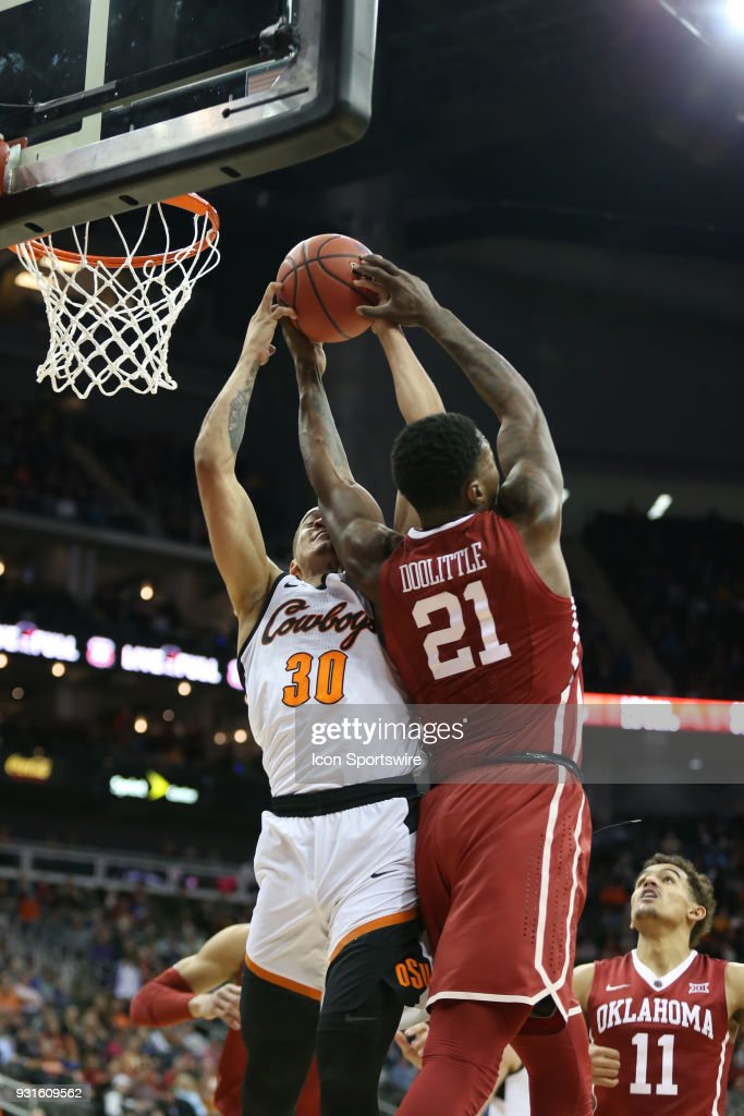 Oklahoma State Cowboys guard Jeffrey Carroll (30) and Oklahoma Sooners forward Kristian Doolittle (21) fight for the rebound in the second half of a first round matchup in the Big 12 Basketball Championship between the Oklahoma Sooners and Oklahoma State Cowboys on March 7, 2018 at Sprint Center in Kansas City, MO. Oklahoma State won 71-60.