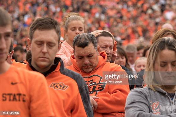 Oklahoma State football fans observe a moment of silence for the people killed by a car that crashed into the homecoming parade during the a NCAA...